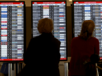 Passengers look at a departure board at Miami International Airport on January 26, 2015 in Miami, Florida. Northeast coast airports are canceling thousands of flights as a major winter storm hits the North East U.S. (Photo by Joe Raedle/Getty Images)