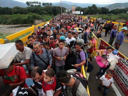 TOPSHOT - Venezuelan citizens cross the Simon Bolivar international bridge from San Antonio del Tachira in Venezuela to Norte de Santander province of Colombia on February 10, 2018. Oil-rich and once one of the wealthiest countries in Latin America, Venezuela now faces economic collapse and widespread popular protest. / AFP …