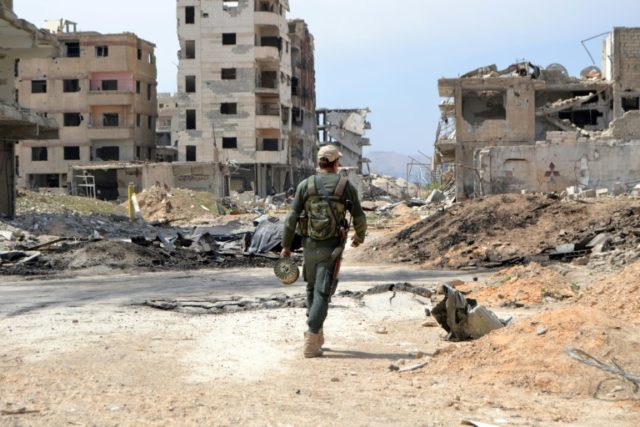 A Syrian government soldier walks past destroyed buildings in the former rebel-held town of Jobar, recently taken by the regime forces, in Eastern Ghouta, on april 1, 2018