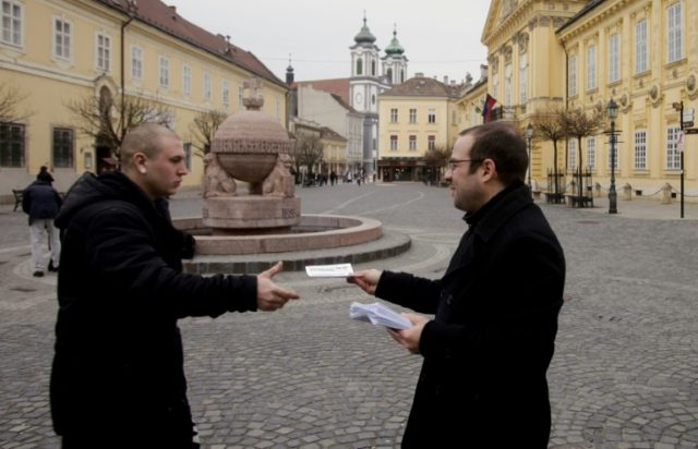 "An activist of ""Print It Yourself!"" hands out home-printed news pamphlets in Szekesfehervar's main square"