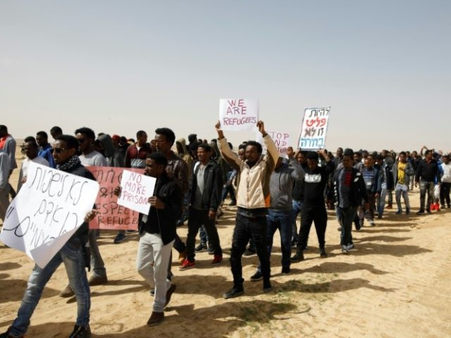 This photo taken on February 22, 2018 shows African migrants marching from the Holot detention centre to the Saharonim Prison, an Israeli detention facility for African asylum seekers