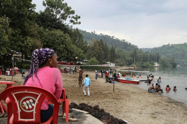 A Congolese woman from Goma city sits on the beach of the Tam Tam resort at Gisenyi in neighbouring Rwanda