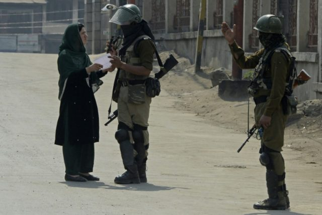 Indian paramilitary troopers stop a Kashmiri woman during a one-day strike called by separatists