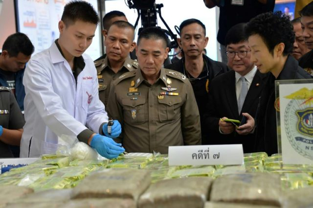 A chemist (L) tests a sample of crystal methamphetamine while Royal Thai national police chief General Chaktip Chaijinda (C) inspects a cache of seized illegal drugs during a press conference in Bangkok on April 3, 2018