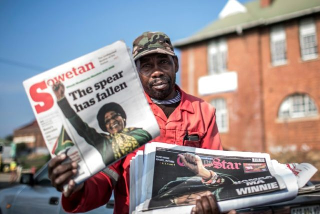 A newspaper seller holds up an edition featuring a story on the death of South African anti-apartheid campaigner Winnie Madikizela-Mandela, in Johannesburg on April 3, 2018