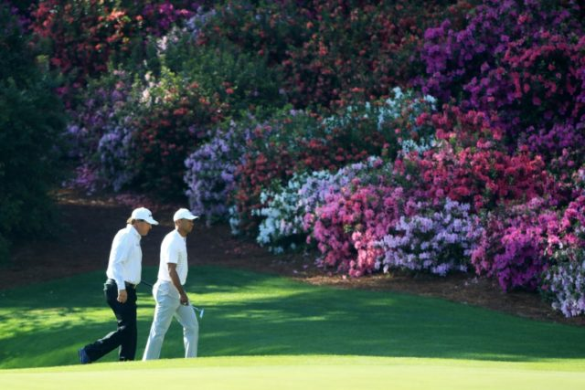 Phil Mickelson (L) of the United States and Tiger Woods of the United States walk onto the 13th green during a practice round prior to the start of the 2018 Masters Tournament at Augusta National Golf Club on April 3, 2018 in Augusta, Georgia