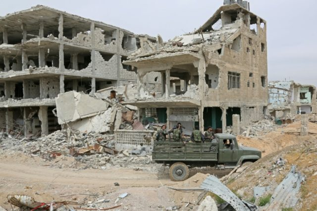 Pro-government forces drive past destroyed buildings in Eastern Ghouta on April 3, 2018