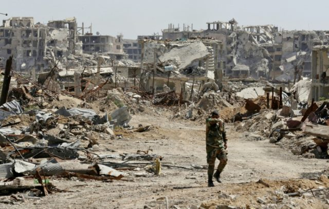 A member of Syrian regime forces walks amid the destruction in Jobar in Eastern Ghouta, on the outskirts of the capital Damascus, on April 2, 2018
