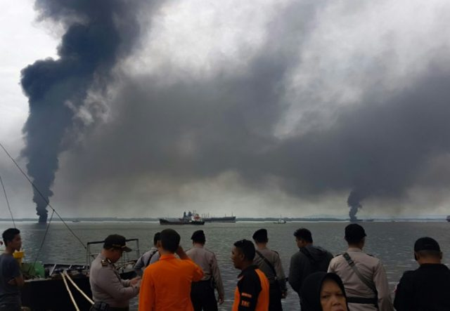 Thick smoke rises from a blaze which broke out during the oil spill cleanup in the waters off Balikpapan