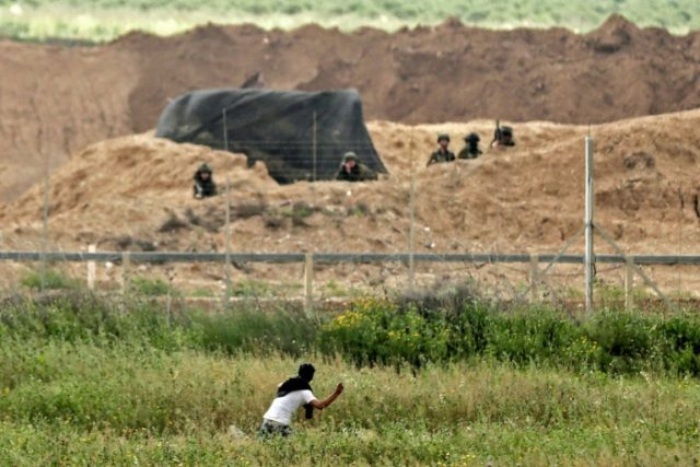 A Palestinian demonstrator throws stones at Israeli soldiers across the border (background) east of Gaza City on March 30, 2018