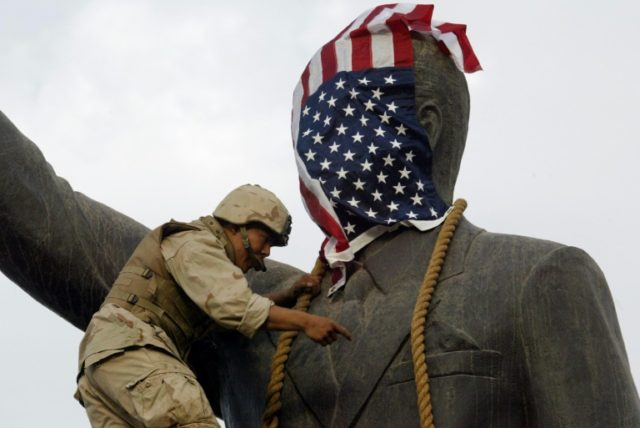 A US Marine covers the head of a statue of Iraqi President Saddam Hussein with the US flag on April 9, 2003 before it is toppled
