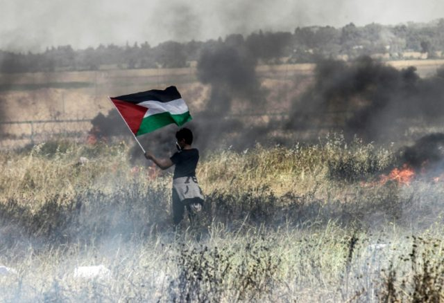 A Palestinian boy holds his national flag during clashes with Israeli security forces on the Gaza-Israel border on April 6, 2018