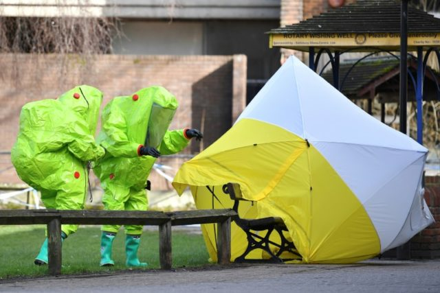 In this photo taken March 8, 2018, emergency services in green biohazard suits re-affix the tent over the bench where former Russian spy Sergei Skripal and his daughter Yulia were found in critical condition on March 4 in Salisbury, England