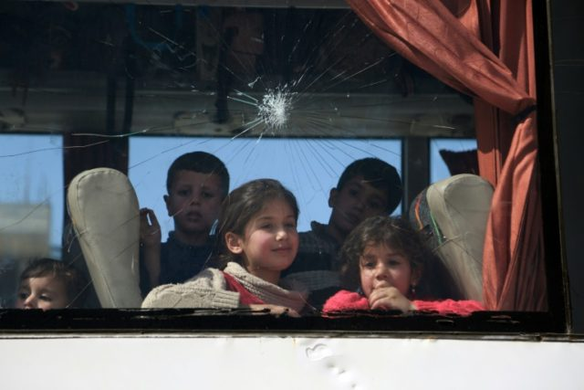 Buses carrying families of fighters from former rebel bastion Eastern Ghouta arrive at a checkpoint in northern Syria on April 5, 2018