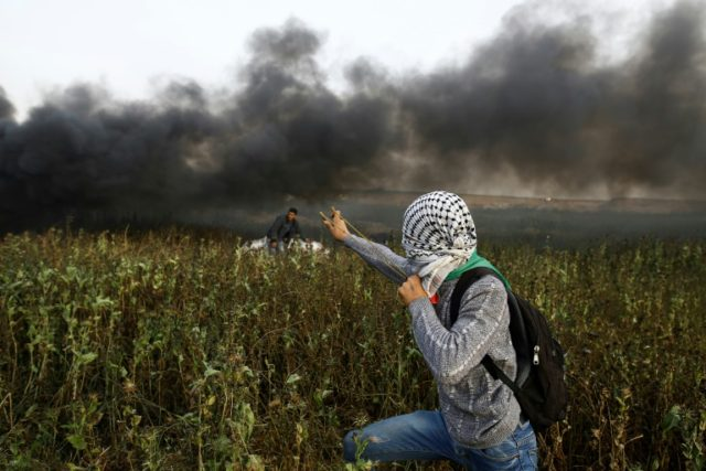 A Palestinian protester uses a slingshot to throw stones towards Israeli forces along the border between the Gaza Strip and Israel on April 5, 2018
