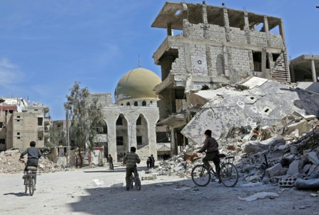 Syrian children ride their bike past destroyed buildings in the former rebel-held town of Zamalka, in Eastern Ghouta on April 5, 2018