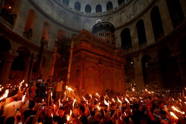 Christian Orthodox worshippers hold up candles lit from the 'Holy Fire' in the Church of the Holy Sepulchre in Jerusalem on April 7, 2018