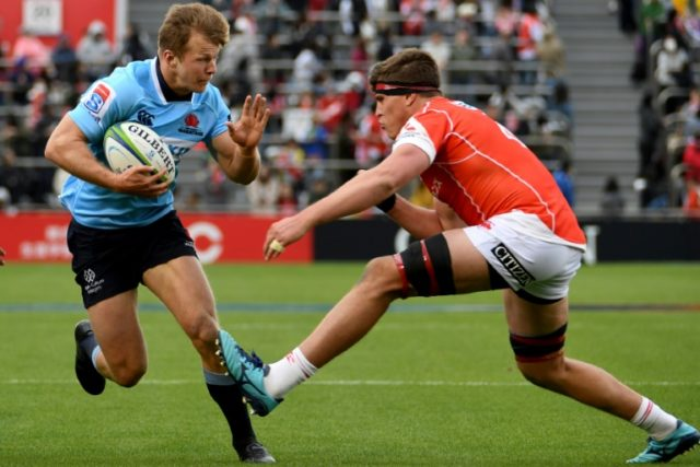 Cameron Clark of the Waratahs (L) hands off James Moore of the Sunwolves during their Super Rugby union match