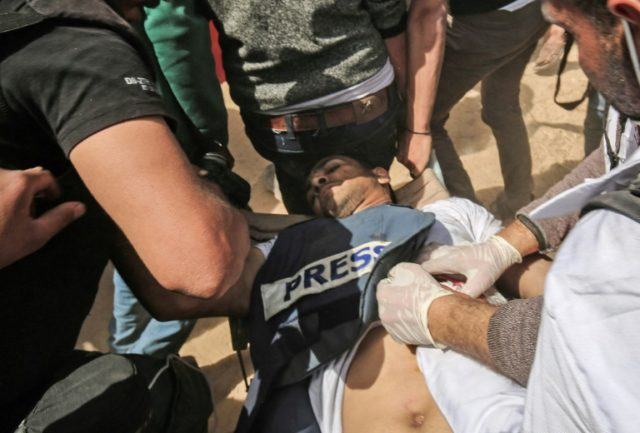 Demonstrators assist wounded Palestinian journalist Yasser Murtaja during clashes with Israeli forces following a protest near the border with Israel on April 6, 2018, Murtaja later died of his wounds, Gaza's health ministry said