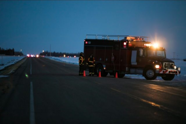 An emergency vehicle is seen near the crash site on April 6, 2018 after a bus carrying a junior ice hockey team collided with a semi-trailer truck between Tisdale and Nipawin, Saskatchewan province, killing 14 people