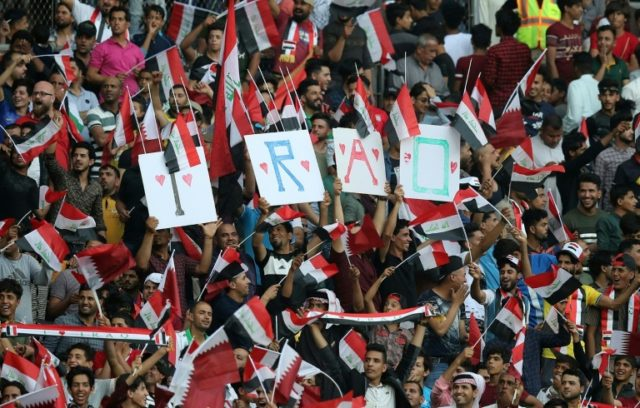 Iraq fans cheer on their team during the international friendly football match between Iraq and Qatar at the Basra Sports City Stadium in Basra on March 21, 2018