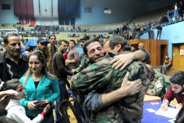 A handout picture released by the official Syrian Arab News Agency shows relatives reuniting after buses carrying detainees released by Jaish al-Islam after being held hostage in the Eastern Ghouta town of Douma arrived in Damascus