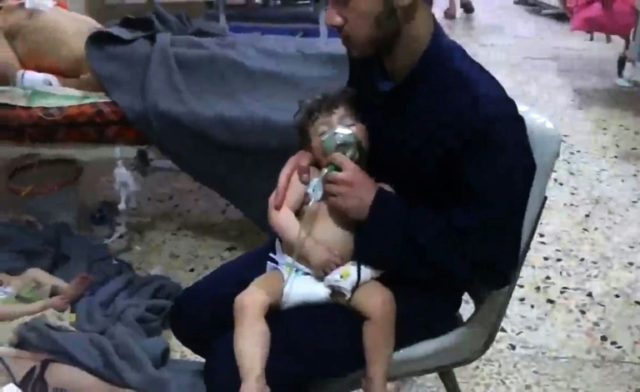 An image grab taken from a video released by the Syrian Civil Defence in Douma shows an unidentified volunteer holding an oxygen mask over a child's face at a hospital following an alleged chemical attack on the rebel-held town