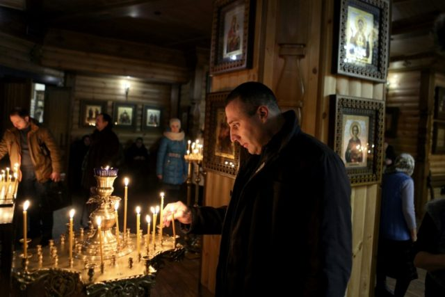 Andrea Palmeri, Italian right-wing hooligan turned pro-Russian fighter, lights a candle inside the Orthodox church in Lugansk in eastern Ukraine, where he fled to in 2014