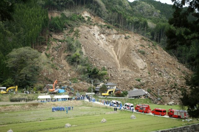 Rescue workers and police search for survivors at the scene of a landslide that hit residential homes in Nakatsu