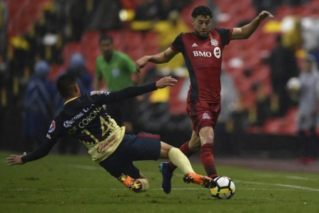 Club America's Joe Corona (L) tackles Toronto FC's Jonathan Osorio during their CONCACAF Champions League semi-final secong leg which Toronto won 4-2 on aggregate