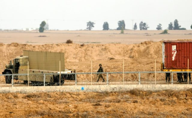 A member of the Israeli forces walks behind a barbed wire fence on the Israeli side of the border with the Gaza Strip on December 10, 2017