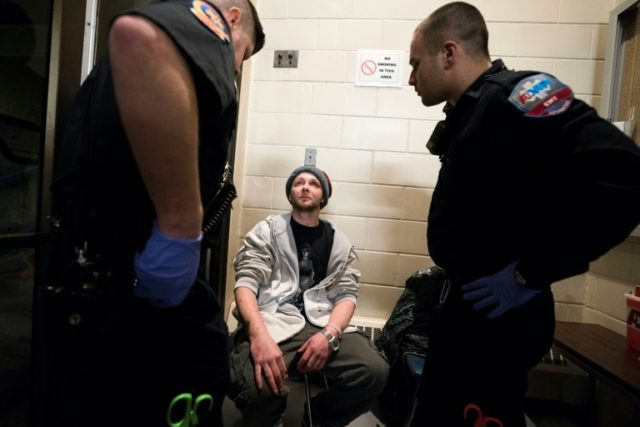 Cody, 31, who fell back into addiction in February, is checked by paramedics as he enters the Safe Station program at the Central Fire Station in Manchester, New Hampshire