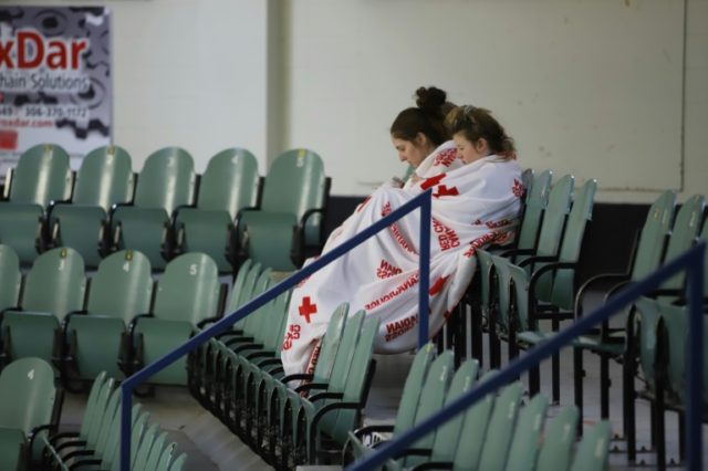 Two girls sit amid empty seats at an ice-skating rink in the small Canadian town of Humboldt, which held an evening vigil to honor the local hockey players and coaches killed in a crash