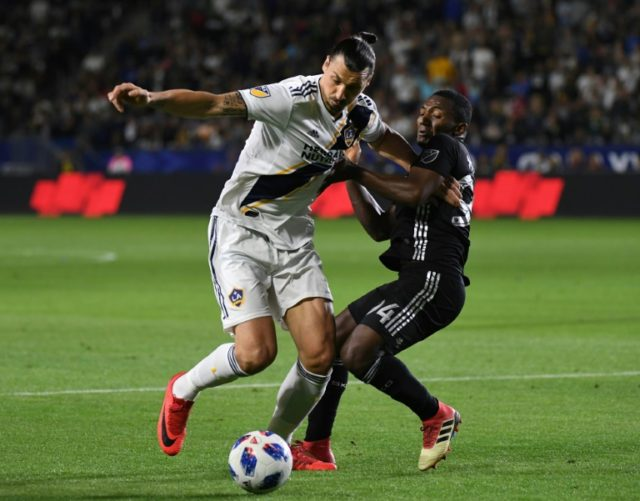 Zlatan Ibrahimovic from LA Galaxy (L) is tackled by Jimmy Medranda of Sporting Kansas City at the StarHub Center