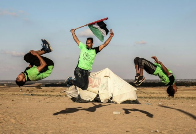 Palestinians perform parkour on the Israeli-Gaza border on April 10, 2018