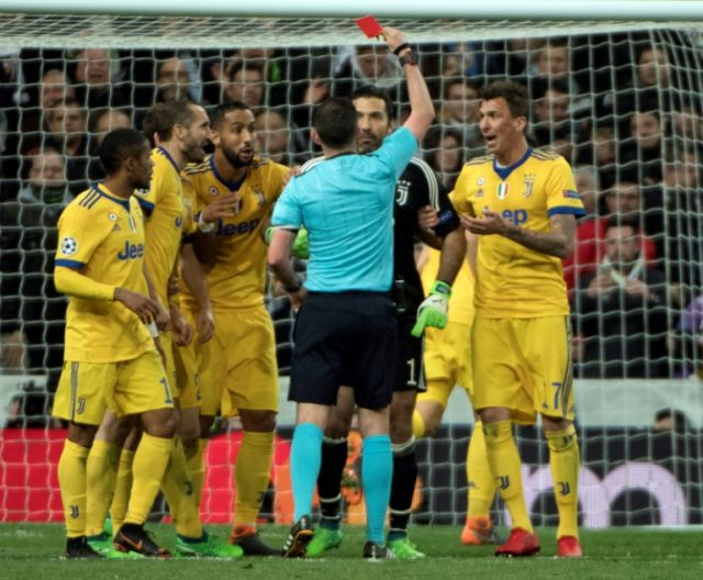 English referee Michael Oliver (C) shows a read card to Juventus' Italian goalkeeper Gianluigi Buffon during a Champions League match on April 11, 2018