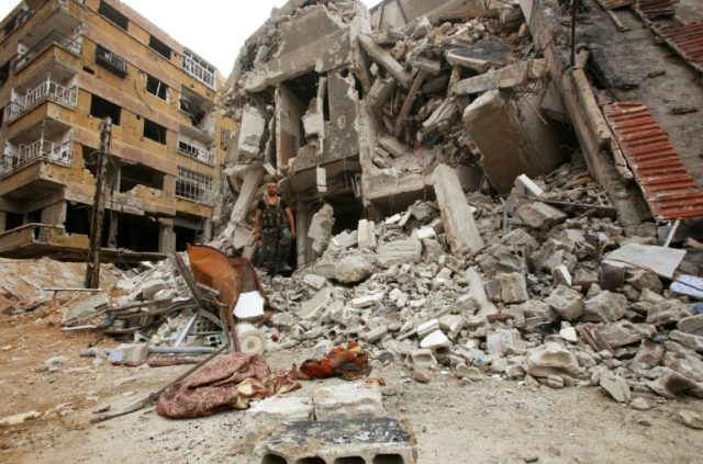 A Syrian soldier walks over the rubble of buildings in the former rebel-held town of Zamalka in Eastern Ghouta, on the outskirts of the capital Damascus on April 11, 2018