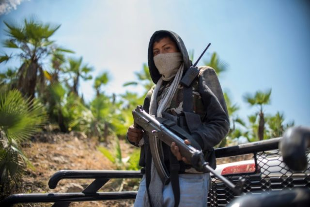 """A vigilante """"community police"""" member stands guard in the hills of Carrizalillo, Guerrero state, Mexico's most violent, where drug cartels and criminal gangs sow terror and citizens say they are standing up to protect their communities"""