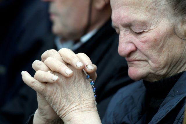 A woman prays at a protest against a treaty safeguarding women before it was passed by Croatia's parliament