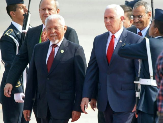 Handout picture released by Andina showing US Vice President Mike Pence (C) upon arrival at the Peruvian Air Force base in Callao, Lima on April 13, 2018, to take part in the Summit of the Americas