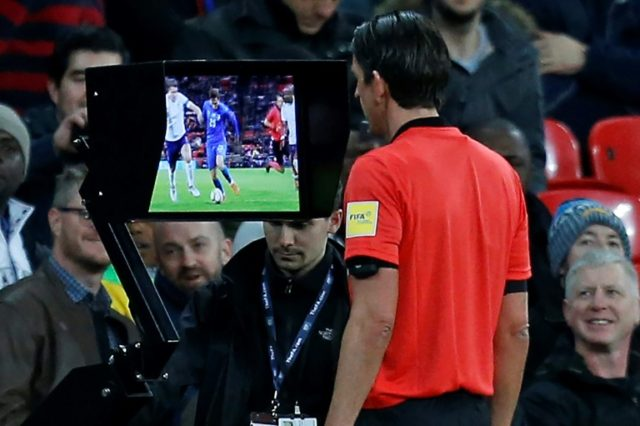 German referee Deniz Aytekin studies the VAR (Video Assistant Referee) screen to see if Italy deserve a penalty against England