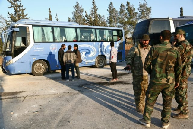 Buses carrying Syrian rebel fighters and their families from their former opposition bastion of Eastern Ghouta arrive at a checkpoint controlled by Turkish-backed rebels in northern Syria on April 13, 2018