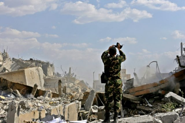 A Syrian soldier inspects the wreckage of a building described as part of the Scientific Studies and Research Centre (SSRC) compound in the Barzeh district north of Damascus, during a press tour organised by the Syrian government after US-led strikes