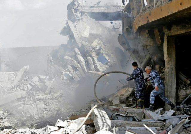 Syrian soldiers inspect the wreckage of a research centre north of Damascus during a government tour on April 14, 2018