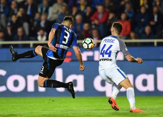 In the air tonight: Atalanta's Brazilian defender Rafael Toloi (left) battles for the ball with Inter Milan's Croatian forward Ivan Perisic