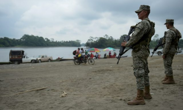 Colombian marines stand guard along the Mira river in Imbili, Tumaco Municipality, in the Colombian department of Narino near the border with Ecuador