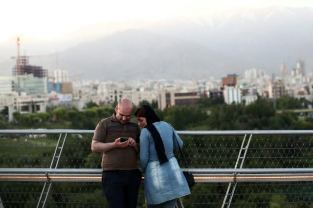 """An Iranian couple look at pictures on their smartphone on the """"Nature"""" bridge in the capital Tehran on May 18, 2017"""