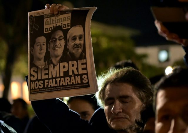 A man holds a newspaper during a tribute to Ecuadorean murdered journalist Javier Ortega, photographer Paul Rivas and their driver Efrain Segarra, in front of Metropolitan Cathedral, in Quito