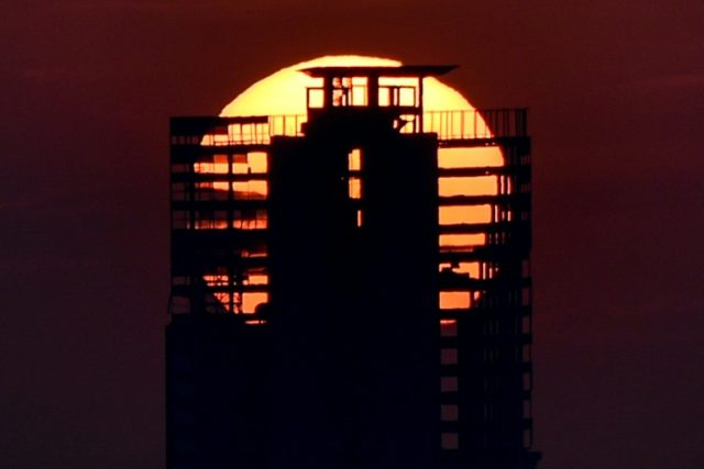 The sun sets behind an abandoned skyscraper in Caracas, known as the Tower of David