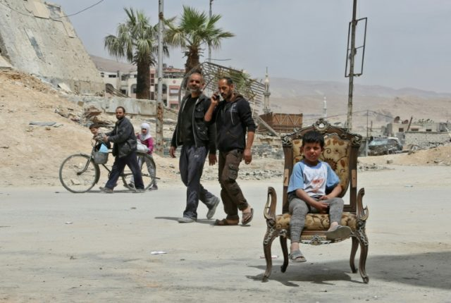 Civilians in the former rebel Syrian town of Douma on the outskirts of Damascus on April 17, 2018 after the Syrian army declared that all anti-regime forces have left Eastern Ghouta